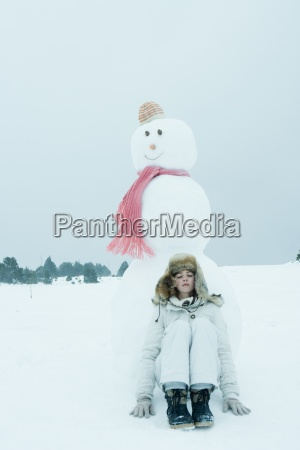 teen girl leaning against snowman