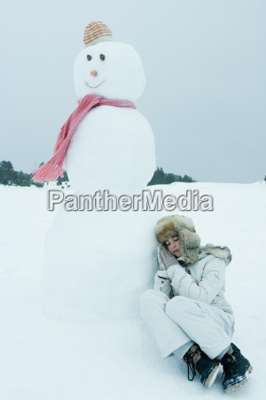 teen girl leaning against snowman sleeping