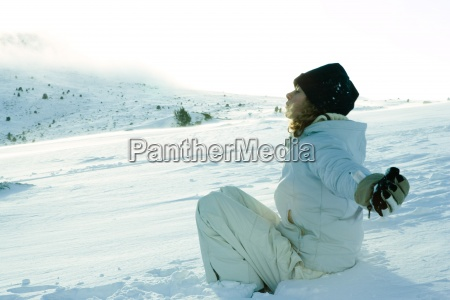 teen girl sitting on snow eyes