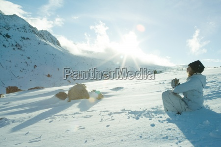 teen girl sitting on snow in