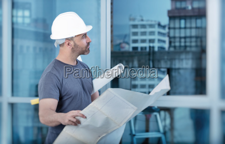 architect builder studying layout plan of