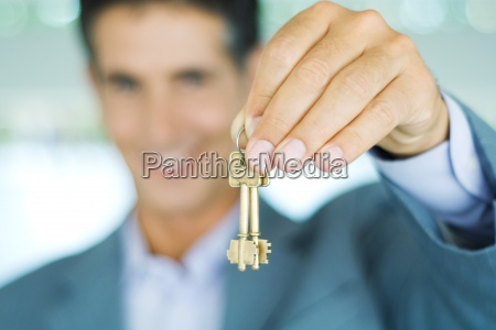 man in suit holding up keys