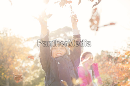 enthusiastic boy playing in autumn leaves