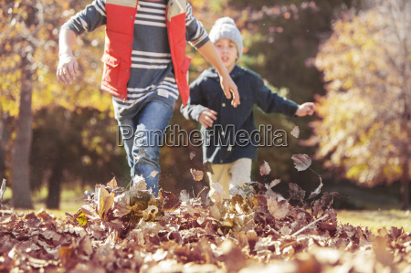 boys running in autumn leaves