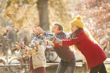 boys and girl catching autumn leaves