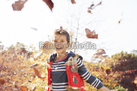 portrait of enthusiastic boy throwing autumn