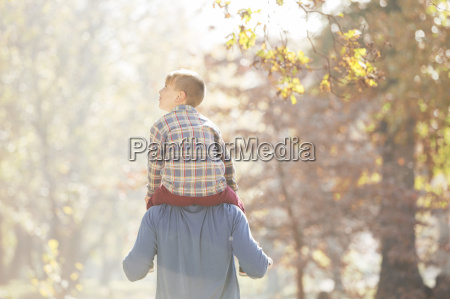 father carrying son on shoulders below