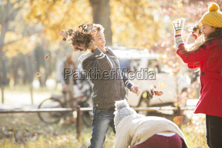 boy throwing autumn leaves at girl