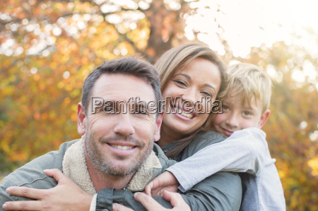 portrait smiling family hugging in front