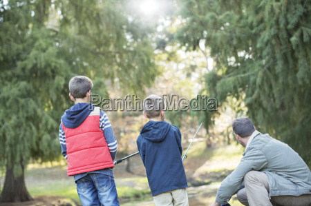father and sons fishing in woods
