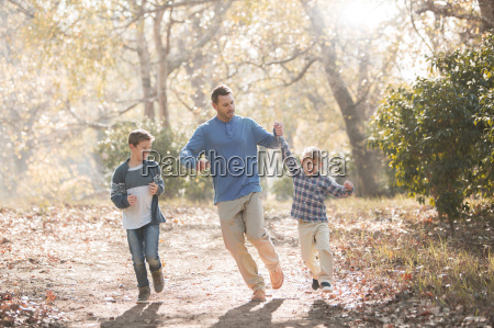 playful father and sons running on