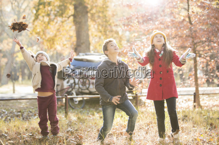 boys and girl throwing autumn leaves