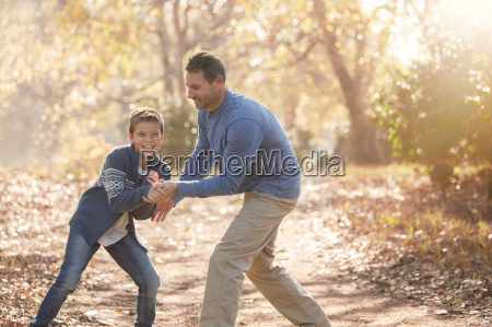 playful father and son on path