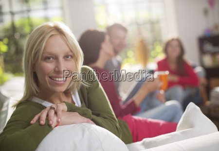 smiling woman sitting on sofa