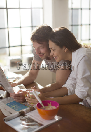 couple reading newspaper together at breakfast