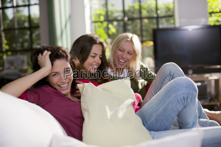 women laughing together on sofa
