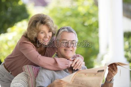senior couple reading newspaper on patio