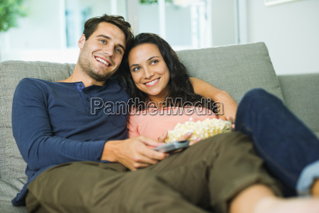 couple watching television on sofa