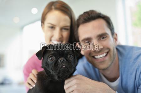 smiling couple petting dog indoors