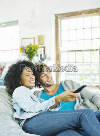 couple watching television in beanbag chair