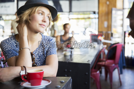 pensive woman in hat with coffee
