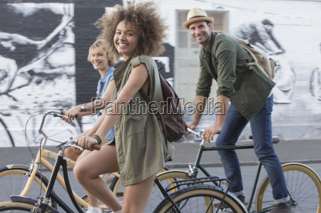 portrait smiling friends riding bicycles on