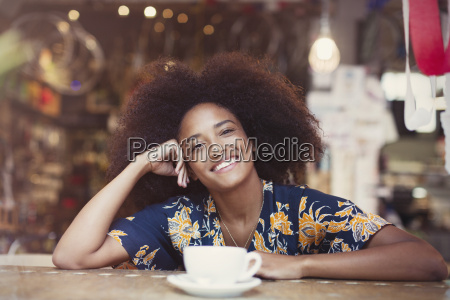 portrait smiling woman with afro drinking