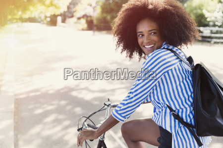smiling woman with afro riding bicycle