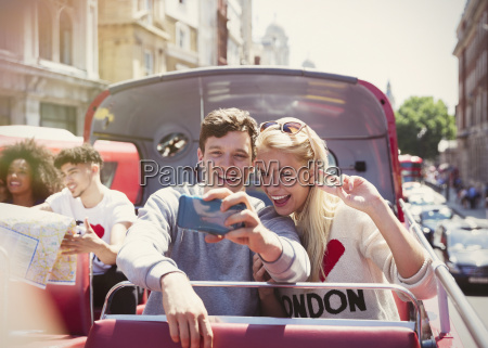 couple taking selfie on double decker