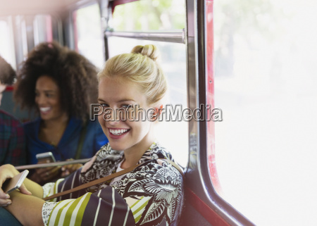 portrait smiling blonde woman riding bus