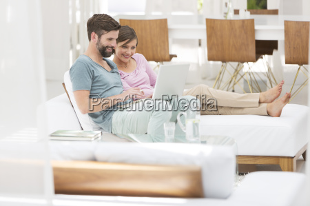 couple using laptop together on daybed