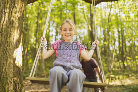 portrait smiling girl swinging on rope