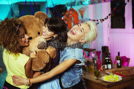 women playing with teddy bear at