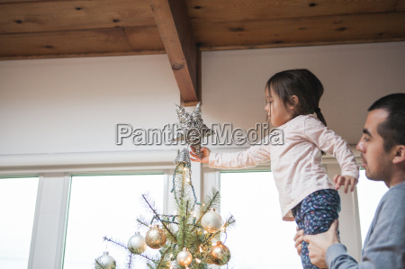 father lifting toddler girl putting star