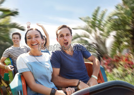 young couple cheering on amusement park