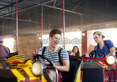 laughing young men riding bumper cars