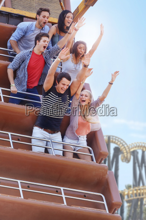 enthusiastic friends cheering on amusement park