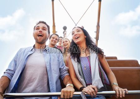 enthusiastic couple riding amusement park ride
