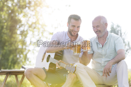 father and adult son toasting beer
