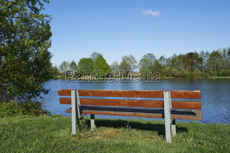 landscape with park bench beside lake