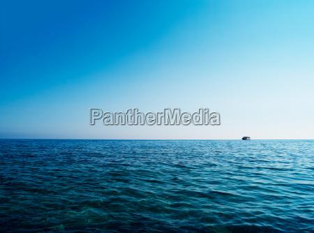 horizontal blue ocean ship on horizon