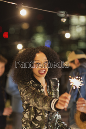 enthusiastic young woman waving sparkler at