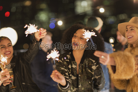 young women waving sparklers at rooftop
