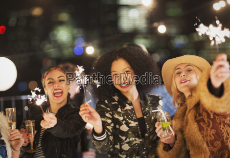 portrait enthusiastic young women waving sparklers