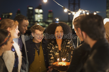 young friends celebrating birthday at rooftop