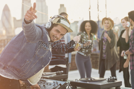portrait enthusiastic dj gesturing at rooftop
