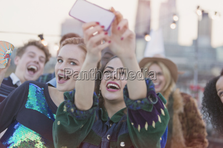 young women laughing and taking selfie