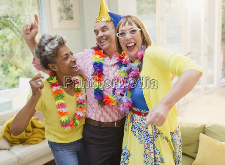 playful mature adults dancing with leis