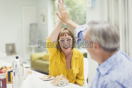enthusiastic mature couple high fiving at