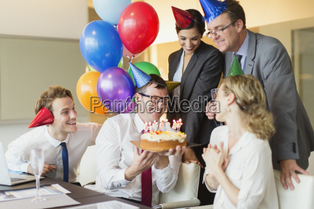 colleagues presenting businesswoman with birthday cake